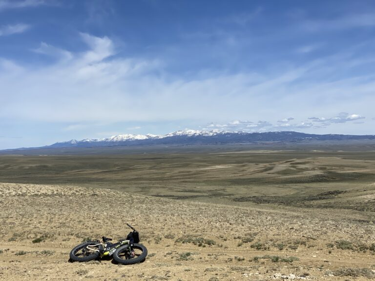 Riding the Continental Divide Trail in Wyoming with Wind River Mountains in the distance.