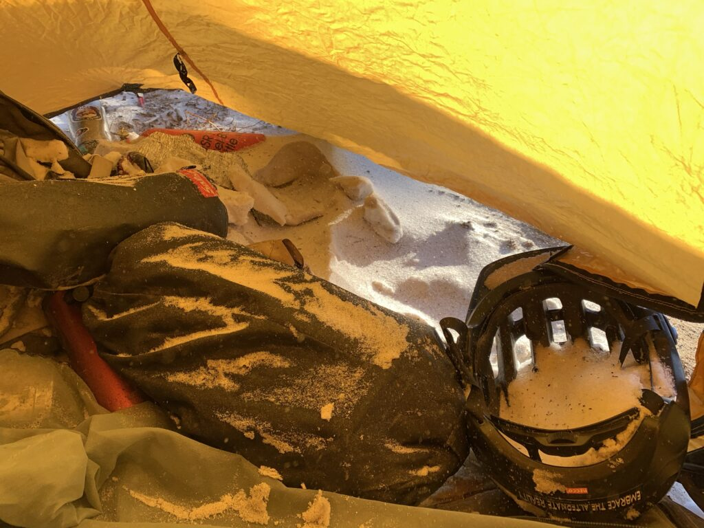 Winter bike packing by fat bike in the Wind River Mountains of Wyoming, tent full of snow.